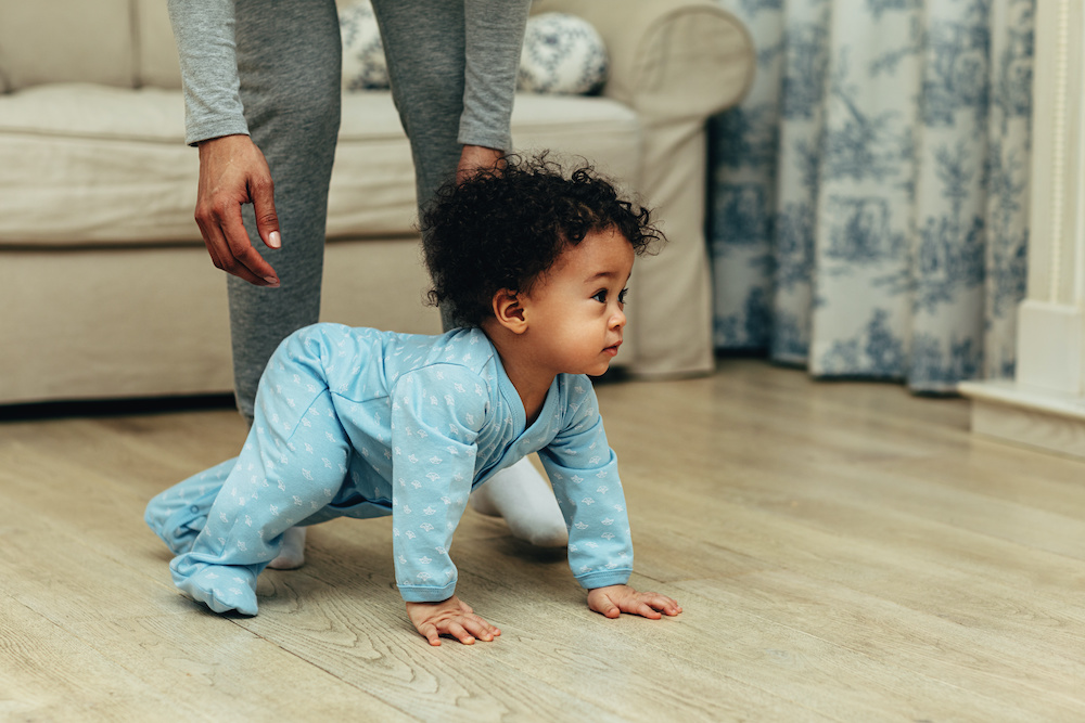 cute baby boy crawling on floor at home